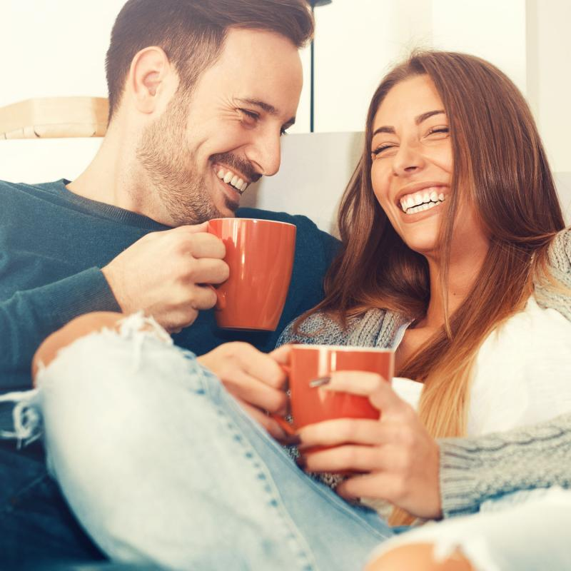 young couple laughing with cups of coffee